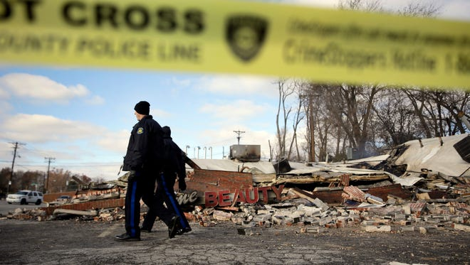Members of the Missouri Highway Patrol walk past a building burned to the ground  Nov. 25 in Dellwood, Mo.