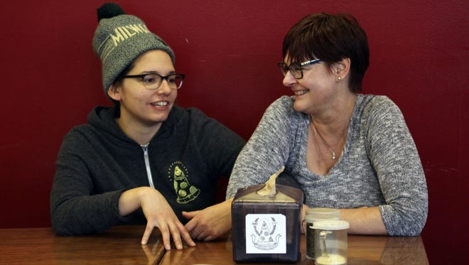 Andrea Ledesma, left, talks with her mom, Cheryl Romanowski, at Classic Slice pizza restaurant, where Ledesma works, in Milwaukee. Ledesma, 28, says her parents owned a house and were raising kids by her age. Not so for her.