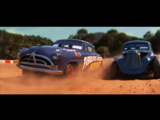 Doc Hudson (left, voiced by Paul Newman) passes his buddy River Scott (Isiah Whitlock Jr.) in a scene from 'Cars 3.'