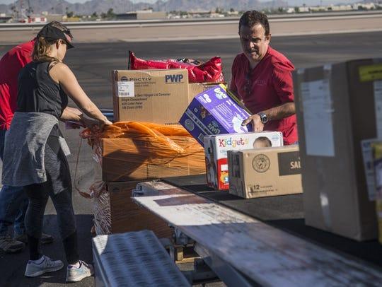 Juan Rodriguez loads diapers onto a conveyor belt up
