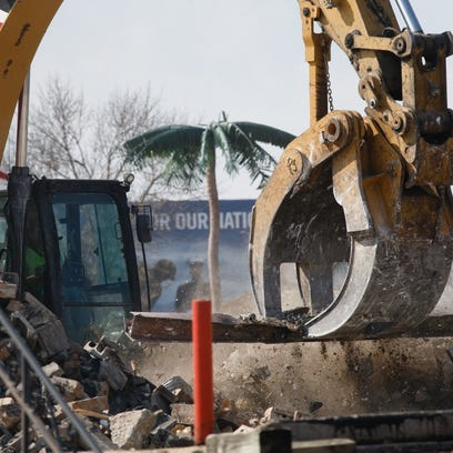 Construction crews tear down the remaining walls of