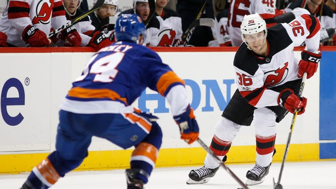 New York Islanders defenseman Thomas Hickey keeps an eye on New Jersey Devils right wing Nick Lappin (36) who skates toward the Islanders' goal during the third period of a preseason NHL hockey game in New York, Monday, Sept. 25, 2017. The Islanders shut out the Devils 3-0. (AP Photo/Kathy Willens)