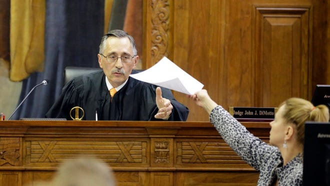 Milwaukee County Circuit Judge John DiMotto presides over court after a verdict was read, Tuesday in Milwaukee, in a negligence lawsuit filed by two Milwaukee police officers who were shot and seriously wounded by a gun purchased at a Wisconsin gun store.