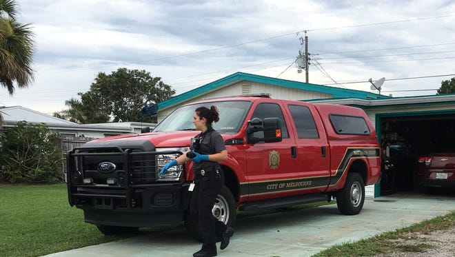 A crime scene technician inspects a Melbourne Fire Department pickup abandoned by a thief.