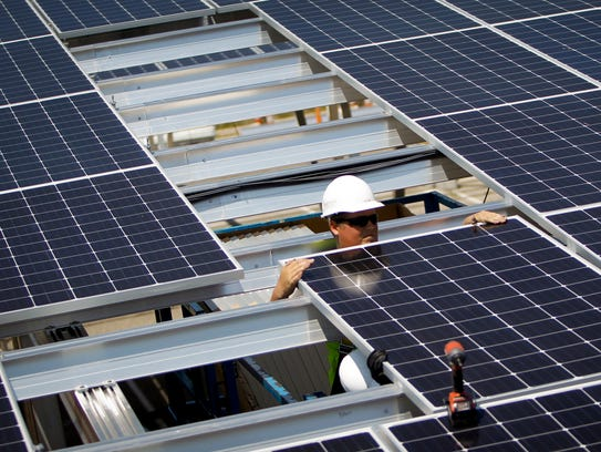 Crews install solar panels above newly created parking