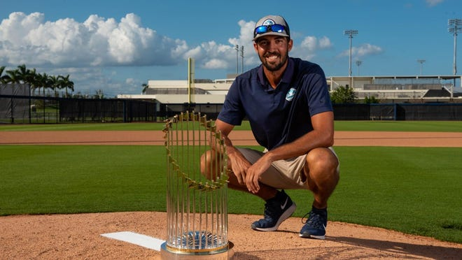 Burlington High School graduate Teddy Gutman poses with the 2019 World Series trophy won by the Washington Nationals.