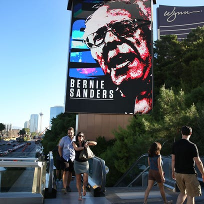 People walk past a billboard with a picture of Bernie Sanders advertising the upcoming Democratic debate at the Wynn Las Vegas resort and casino on Oct. 12, 2015, in Las Vegas.