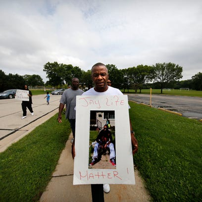 Jay Anderson Sr., father of Jay Anderson, holds a poster with a photograph of his son as he leads a small protest in and around Madison Park Saturday, Aug. 27, 2016, in Wauwatosa, Wisconsin. Jay Anderson was killed by a Wauwatosa Police Officer in the park in the early hours of June 23. The shooting remains under investigation.