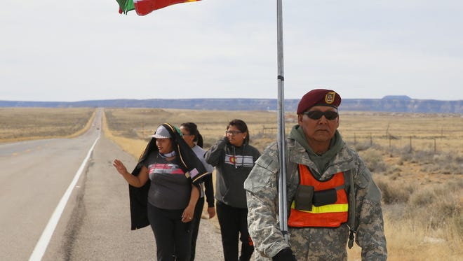 Army Sgt. Anderson Jim, center, carries U.S. and Vietnam War veterans flags during a walk Saturday to honor Vietnam veterans on N.M. Highway 371 near Crownpoint on Saturday. The walk started on March 24 in Thoreau and will end on Wednesday in Shiprock.