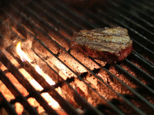 A steak sizzles on the grill at Rube's Steakhouse in