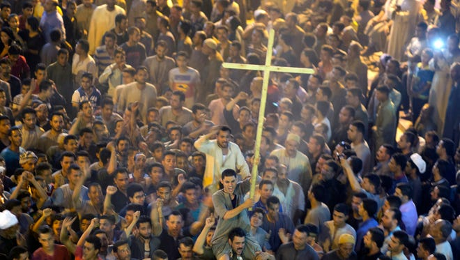 Coptic Christians shout slogans after the funeral service of some of the victims of a bus attack, at Abu Garnous Cathedral in Minya, Egypt,  May 26, 2017.
