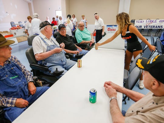 Mikayla Burch, a waitress at Hooters, serves drinks to residents from the Missouri Veteran's Home in Mt. Vernon at Elks Lodge #409 as they hosted a barbecue and wings from Hooters for the veterans on Wednesday, July 11, 2018.
