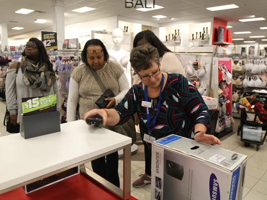 Susan Lukasiewicz, checks the price of the Samsung soundbar for Sharlene Banks, center, of Rochester.  Banks was shopping with Racheal Washington of Fairport and Washington's daughter, Aja Williams at Koh's.