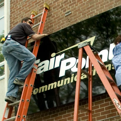 Workers install the new FairPoint Communications sign