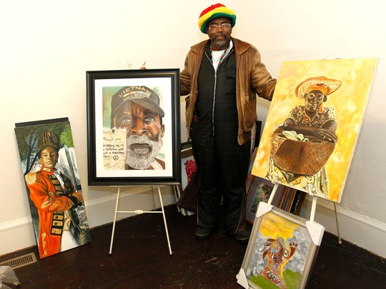 """Willie Weaver-Bey shows four of the several hundred paintings in his new home in the Sherman Park neighborhood. His painting, """"A Veteran, Not Homeless,"""" shown at his right, earned first place in the pastels category at the 2016 National Veterans Creative Arts Festival."""
