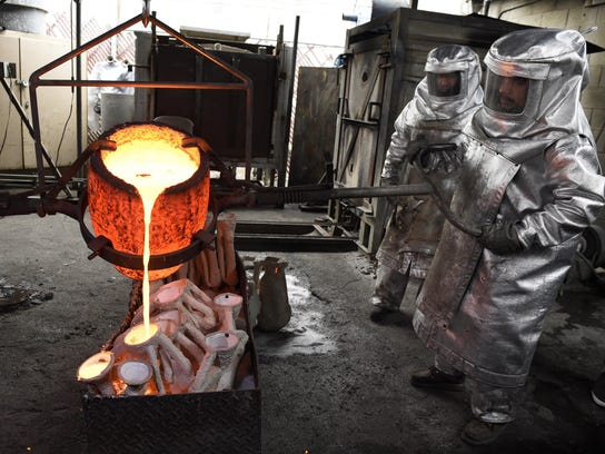 Workers pour molten bronze metal into molds to make