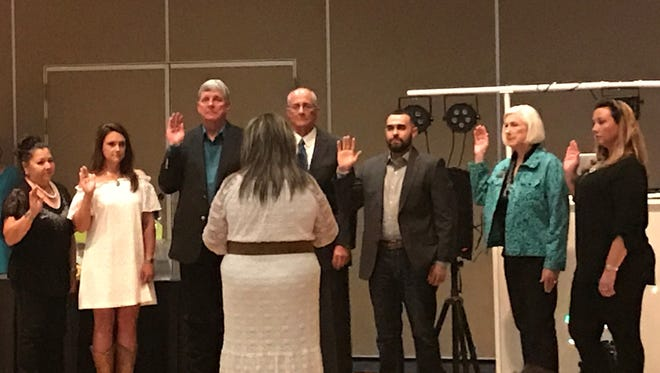 Outgoing president Irma Devine administers the oath of office to the new members of the board of directors of the Ruidoso Valley Chamber of Commerce.