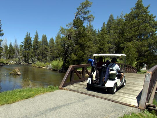 Golfers in carts use a bridge to cross the Upper Truckee