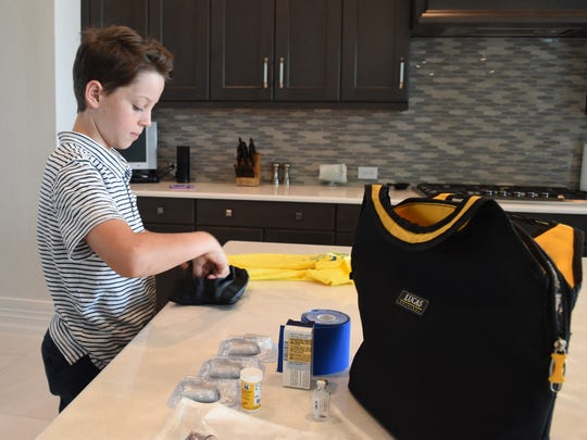 Lucas Lye, 12, packs his traveling essentials for his