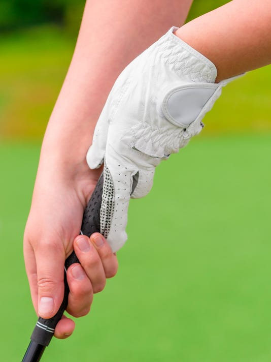 woman's hands holding putter close-up shot