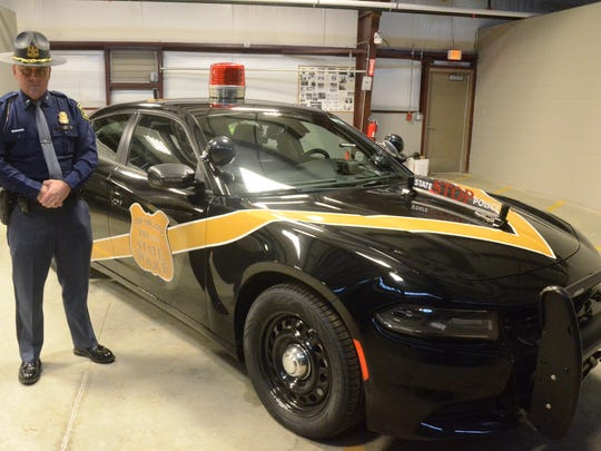 MSP First Lt. James Coleman, wearing the new campaign hat,  with one of the new 100th Anniversary patrol cars.