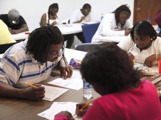 Students work on a science problem in their adult education class at the Inner Faith Gospel Tabernacle.