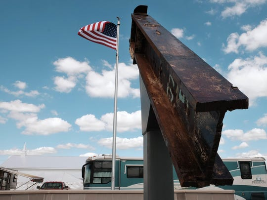 """This Sept. 3, 2016 photo shows a beam from the destroyed World Trade Center buildings, part of the 9/11 Memorial near the Veterans' Pavilion at the Fulton County Fair, in Wauseon, Ohio. """"We just don't know where the events of 9/11 have lead us,"""" said Rick Sluder, fire chief in Wauseon, Ohio, which obtained the beam and, together with neighboring departments built the memorial. """"A lot of people are looking at this as, is this point of downfall or the point at which we rose above the rest, the point of resiliency?"""" Sluder said. """"I don't think that's been determined yet."""" (Jetta Fraser/The Columbus Dispatch via AP)"""