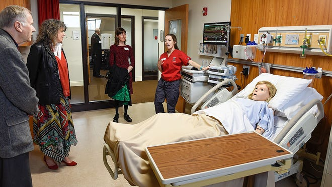 Nursing student Katie Nosbush, right, describes the equipment in one of the patient rooms during a tour of the newly renovated nursing department facilities Thursday, April 21, in the Main Building at the College of St. Benedict in St. Joseph.