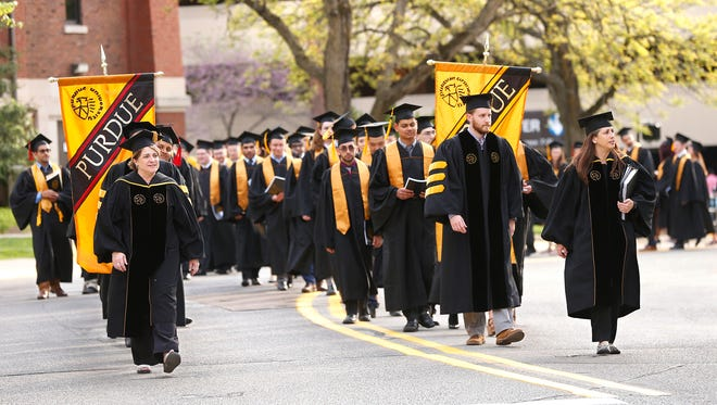Graduates march from the Purdue Amory to Elliott Hall of Music for evening commencement ceremonies Friday, May  11, 2018, on the campus of Purdue University.