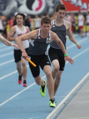 Ankeny Centennial's Nick Paulson takes the baton from Tanner Strumm to start the final leg of the 4x800 relay at the Class 4-A co-ed state track meet at Drake Stadium in Des Moines.  They joined Jorvik Harris and Zach Wolfe to finish 15th in a time of 8:09.42. May 22, 2014
