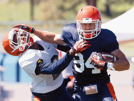 MARK LAMBIE-EL PASO TIMES  UTEP wide receiver Cole Freytag stiff-arms defensive back Ishmael Harrison during action Wednesday at Camp Ruidoso.