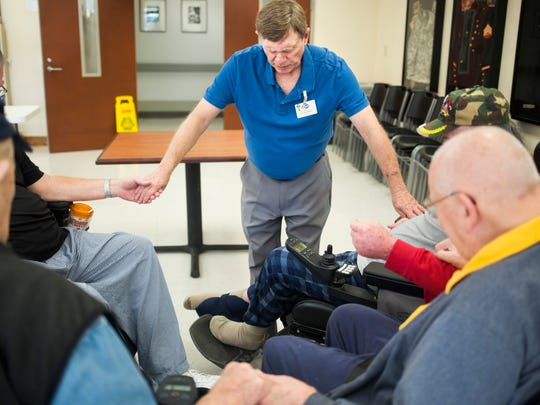 Steve Cannon, war veteran and chaplain at the Richard M. Campbell Veterans Nursing Home, prays with a group of veterans.