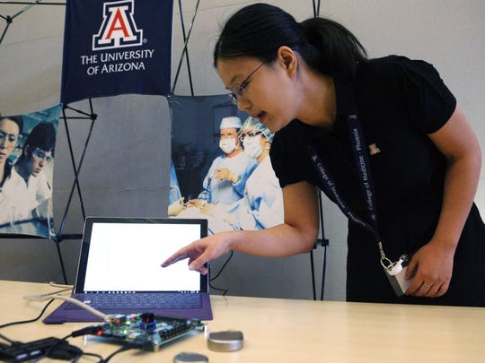 Sixing Lu, a fourth-year graduate student at the University of Arizona, shows how she hacked into the pacemaker on the table during the CyberMed Summit on June 8, 2017. Doctors, hackers and medical-device manufacturers came together for the two-day summit, which was held at the University of Arizona College of Medicine --  Phoenix. The event hopes to start conversations about how to protect medical technology from cyberattacks.