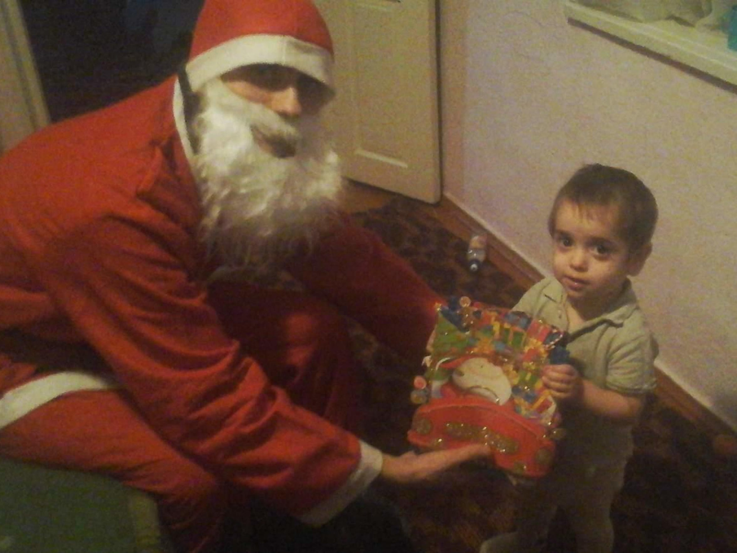 Victor Malac dresses as Santa to give his children bags of candy at their Moldovan house last year on Christmas. It was the family's last Christmas in Moldova.