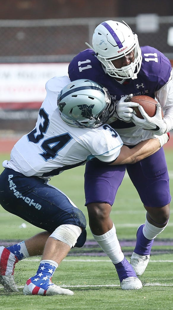 New Rochelle's Khairi Manns (11) gets tackled by John