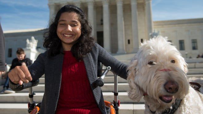 Ehlena Fry, 12, of Michigan, sits with her service dog Wonder outside the Supreme Court in October, when her case was argued.