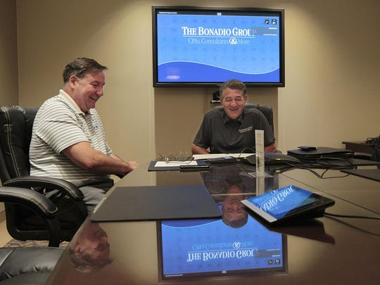 Tom Bonadio, CEO of the Bonadio Group, right, and Carl Cadregari, executive vice president, share a laugh during a conference call with a client at the Bonadio Group offices in Perinton on Tuesday.