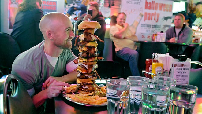 Jeremiah Forster participates in the Dave burger challenge Thursday at Shooter's Saloon. The burger consists of one-third pound burger patties, cheese slices, bacon on every other patty, onion on every other patty, smothered in barbecue sauce and served with half a pound of fries.