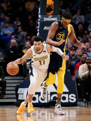 Denver Nuggets guard Jamal Murray (27) dribbles the ball up court as Indiana Pacers center Myles Turner (33) defends in the first quarter at the Pepsi Center.