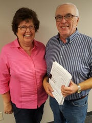 Barb and Sam Morgan pose for a photo at the Wausau Daily Herald office on Aug. 11, 2016, with the petition they worked on in 2006 to require referendums in Wausau for fees on taxpayers.