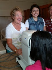 Kathy uses an autorefractor to get a young Nicaragua girl's approximate eyeglass prescription during a recent trip to the country.