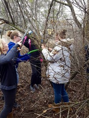 Mishicot Middle School students used loppers and handsaws to remove invasive honeysuckle from the forest at Woodland Dunes Nature Center & Preserve in Two Rivers.