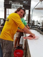 Steven Cooper cleans red snapper from the fresh catch