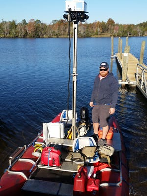 Ryan Abrahamsen, the owner of Terrain360, a an independent virtual tour company that is helping map the Blackwater River, stands with his rig and boat on the river in an undated photo.