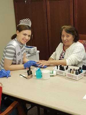 """Miss Vineland Sarah Layton visits the residents of Baker Place in Vineland twice a month and offers complimentary manicures and her smile.Her platform is """"People, Too."""" She is bringing awareness to the fact that everyone deserves respect and dignity regardless of differences, including age or disability.Theresa Infante receives a manicure from Miss Vineland during a recent visit."""