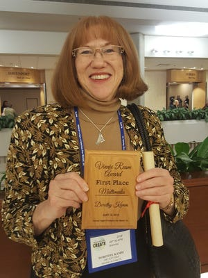 Dorothy Kamm proudly displays the sterling silver harp pendant and plaque she received for her first place award in the Arts and Letters Multi-Media category of the Vinnie Ream Medal Competition sponsored by the National League of American Pen Women.