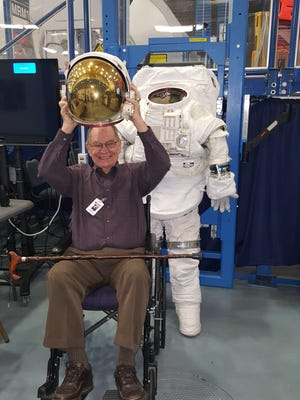 John Fabac, a former IBM employee at the Kennedy Space Center in Cape Canaveral, Fla., tries on an astronaut's helmet during a visit to Houston's NASA Johnson Space Center in 2017.