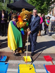 Champlain College President Donald J. Laackman is joined by mascot Chauncey T. Beaver and superhero Prism (Carol Moran Brown) for the ceremonial start of painting the rainbow crosswalk.