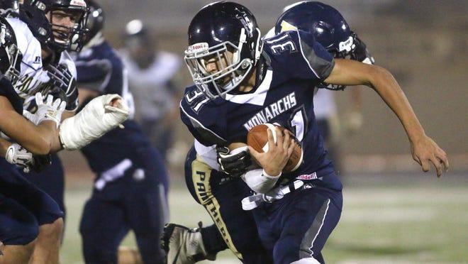 Thomas More Prep-Marian High School quarterback Kade Harris looks to get past Phillipsburg High School defenders during a game last season at Lewis Field Stadium.