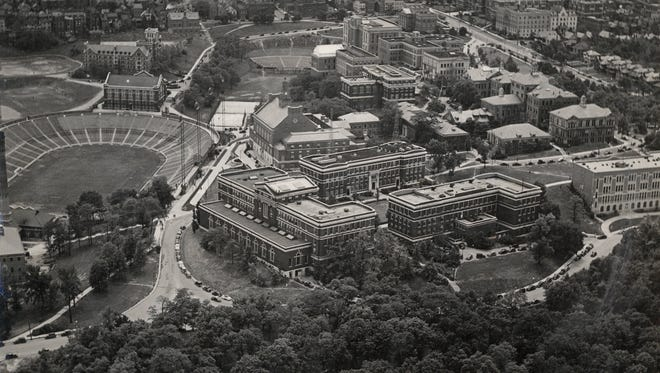 An aerial view of the University of Cincinnati campus, facing south circa 1937, features the engineering quadrangle and Student Union Building in the center.